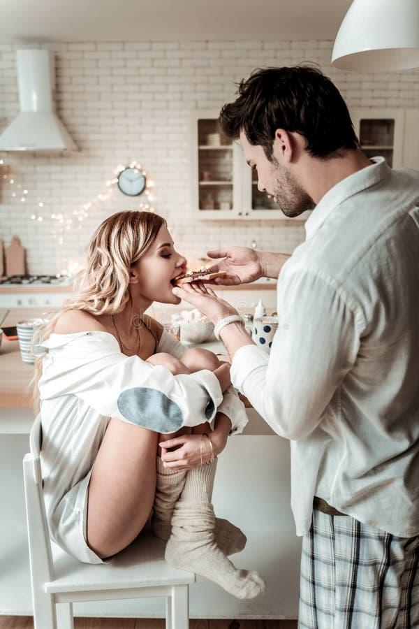 Donkerbruine gebaarde mens in een wit overhemd die een sandwich geven aan zijn vrouw stock afbeeldingen