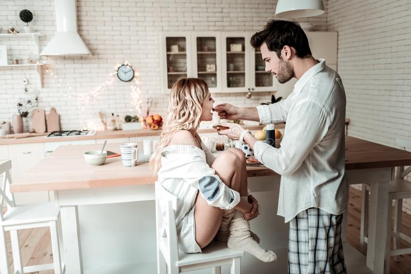 Donkerbruine gebaarde mens in een wit overhemd die zijn vrouw in de keuken voeden royalty-vrije stock fotografie