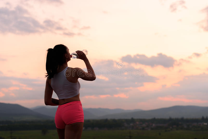 Donkerbruine geschiktheids sexy vrouw die en in openlucht in zonlicht uitoefenen ontspannen stock fotografie