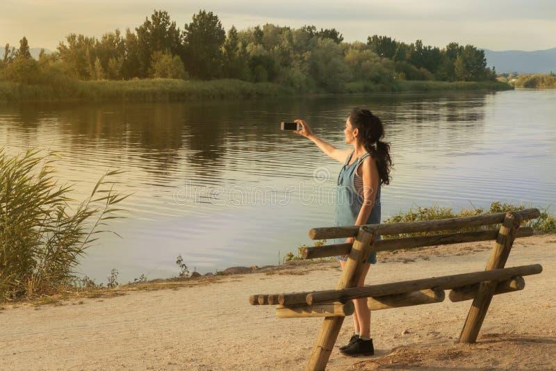 Donkerbruine jonge vrouw die een landschap met rivier fotograferen stock afbeeldingen
