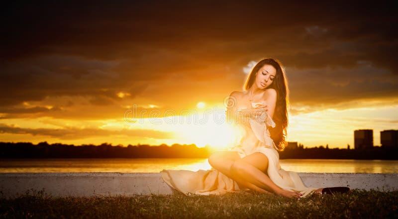 Donkerbruine Kaukasische vrouw in kleding stellen provocatively openlucht voor een mooie zonsondergang. Mooi blootvoets meisje die royalty-vrije stock fotografie