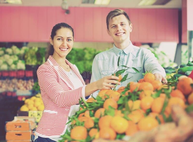 Donkerbruine meisje en het glimlachen vriend het kopen citrusvruchten stock fotografie