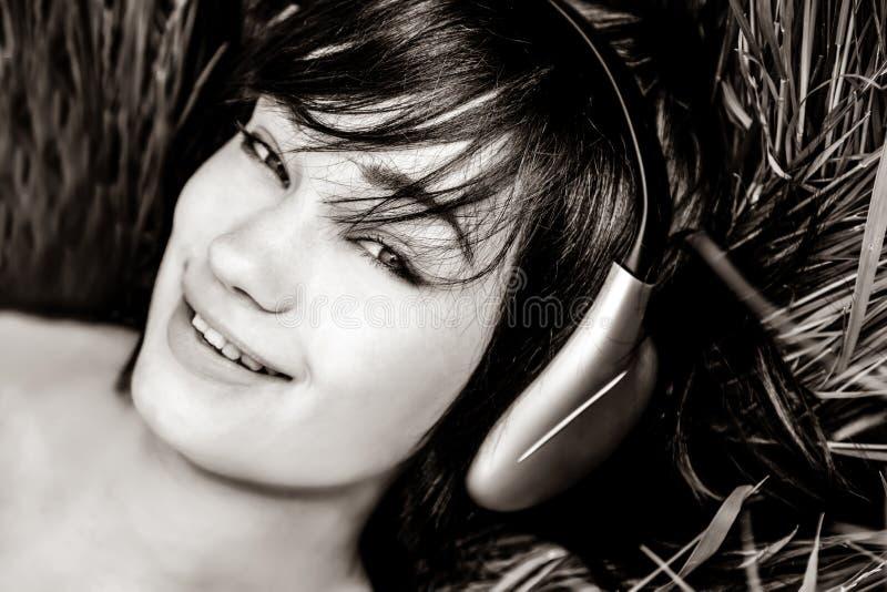 Donkerbruine meisje het luisteren muziek bij gras royalty-vrije stock afbeeldingen