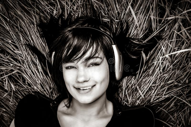 Donkerbruine meisje het luisteren muziek bij gras stock afbeelding