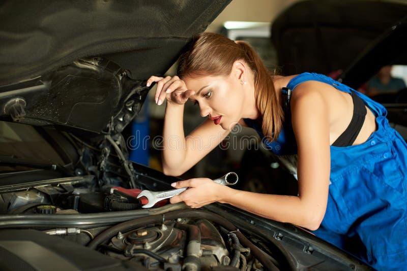 Donkerbruine meisjeswerktuigkundigen die of een auto herstellen inspecteren royalty-vrije stock foto's