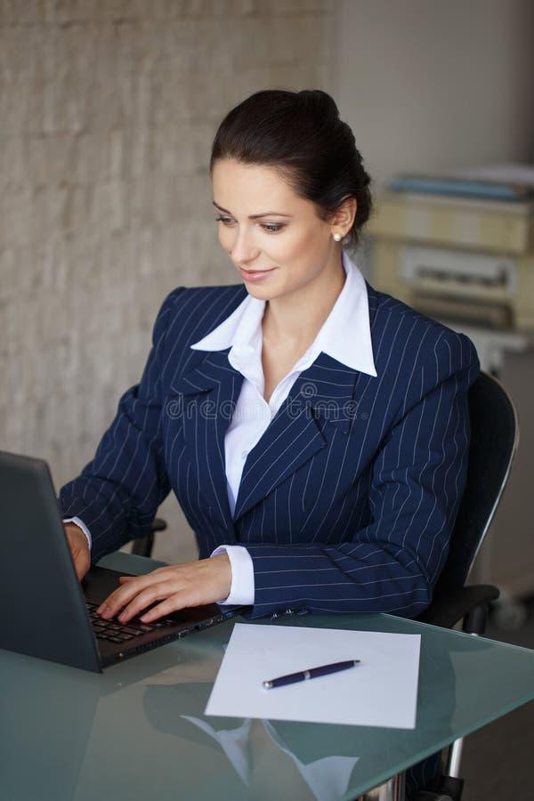 Donkerbruine secretaresse het typen brief op laptop stock afbeelding