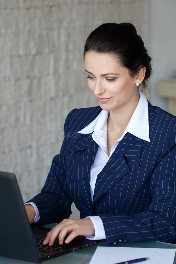Donkerbruine secretaresse het typen brief op laptop stock afbeeldingen