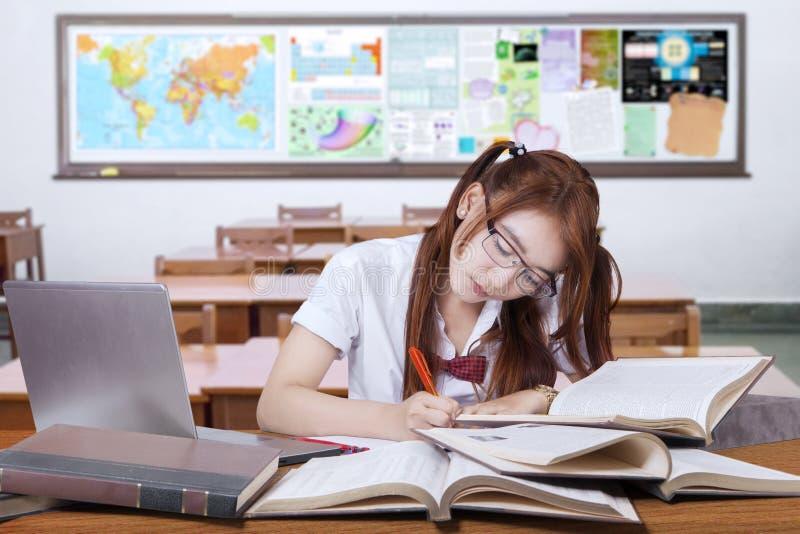Donkerbruine student die haar taak in de klasse doen royalty-vrije stock foto's