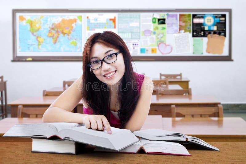 Donkerbruine student met boeken op de lijst in klasse royalty-vrije stock afbeelding