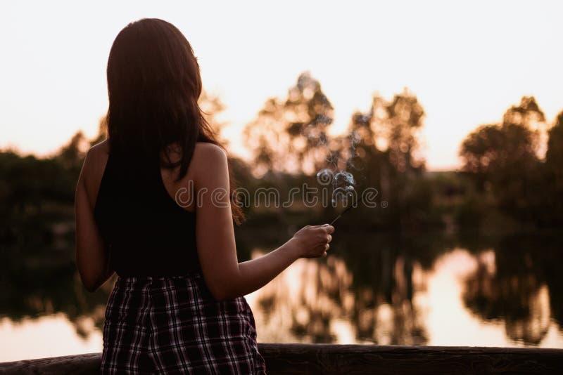 Donkerbruine vrouw bij zonsondergang op een meer met een wierookstok stock afbeelding