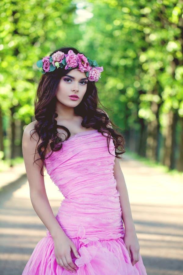 Donkerbruine vrouw in bloemenkroon en roze kleding openlucht royalty-vrije stock foto