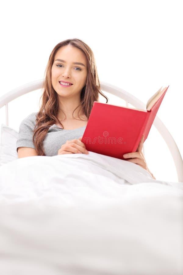 Donkerbruine vrouw die in bed liggen en een boek houden royalty-vrije stock afbeeldingen