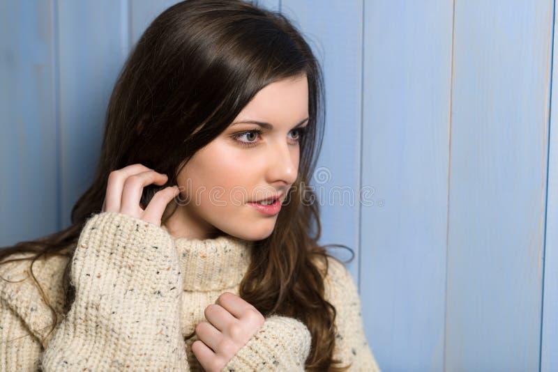 Donkerbruine vrouw die in beige sweater opzij kijkt royalty-vrije stock fotografie