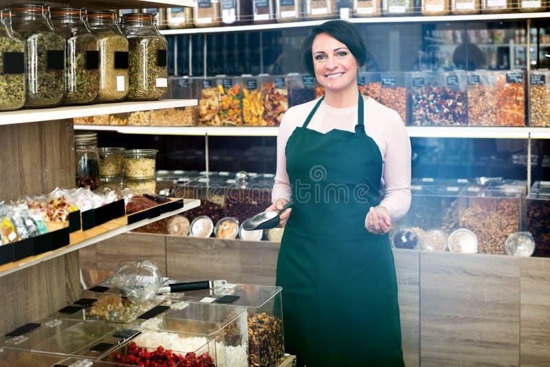 Donkerbruine vrouw die schort dragen en noten verkopen royalty-vrije stock foto