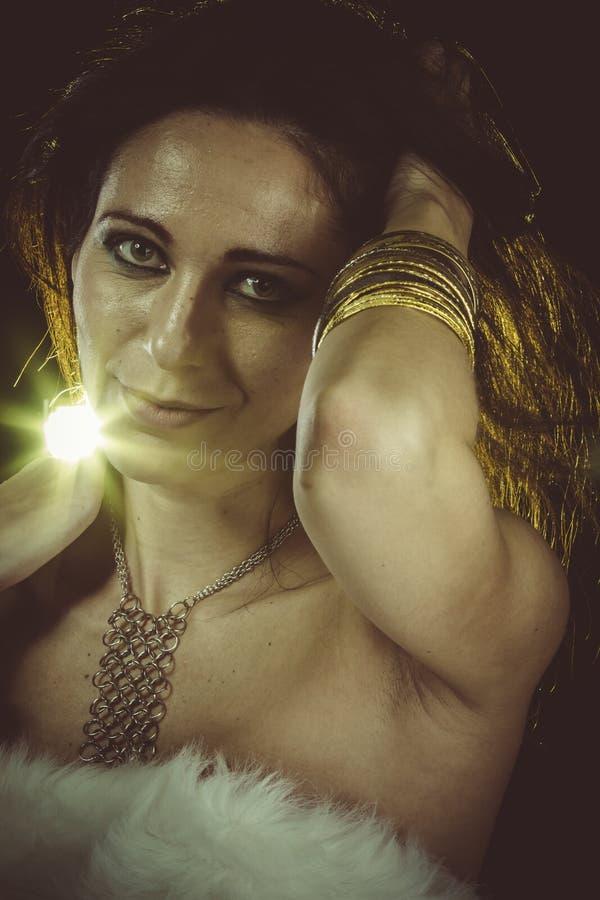 Donkerbruine vrouw die wit bont en gouden juwelen dragen royalty-vrije stock afbeelding
