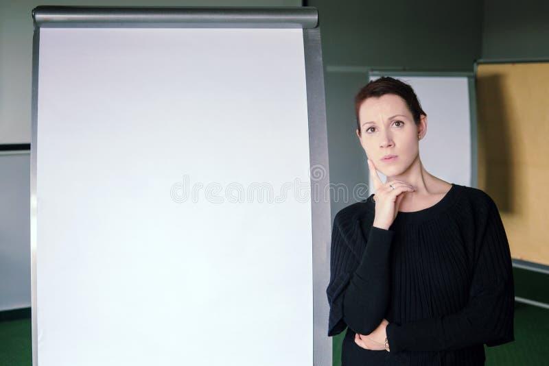 Donkerbruine vrouw die zich naast een flipchart in bureau bevinden royalty-vrije stock foto's