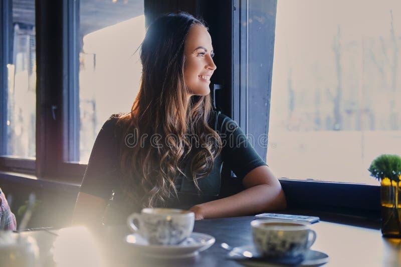 Donkerbruine vrouw in een koffie stock afbeelding