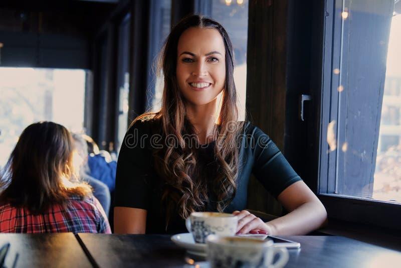 Donkerbruine vrouw in een koffie stock foto