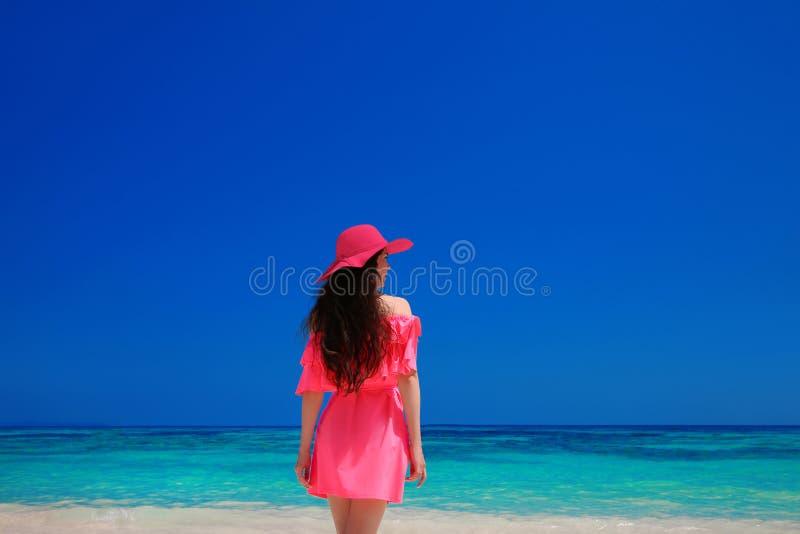Donkerbruine Vrouw enjoyng op Tropisch Strand Aantrekkelijk meisje in rood royalty-vrije stock foto