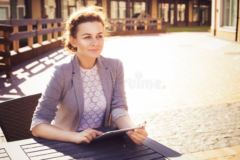 Donkerbruine vrouw in grijs jasje, donkere broeken en witte blouse met tablet in openlucht De ruimte van het exemplaar royalty-vrije stock foto