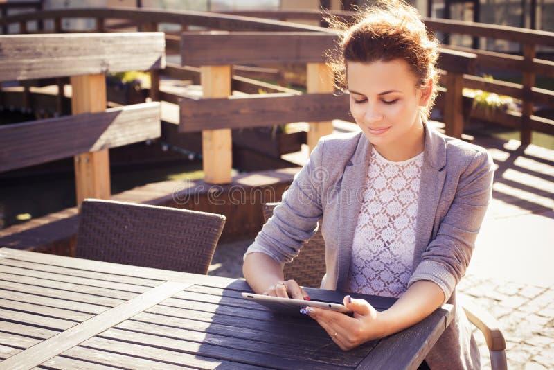 Donkerbruine vrouw in grijs jasje, donkere broeken en witte blouse met tablet in openlucht De ruimte van het exemplaar stock afbeeldingen