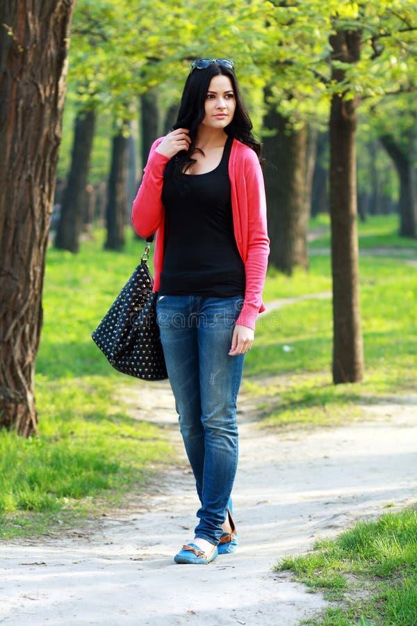 Donkerbruine vrouw in het park stock afbeelding