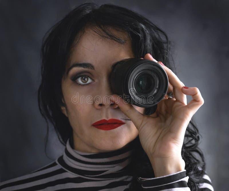 Donkerbruine vrouw met cameralens in haar oog stock afbeelding
