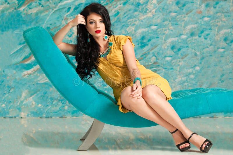 Donkerbruine vrouw met het lange haar ontspannen op moderne stoel stock fotografie