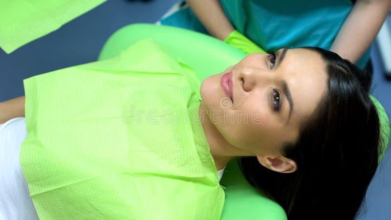Donkerbruine vrouwelijke patiënt die op injecties in lippen wachten, de kosmetiekprocedures stock foto's