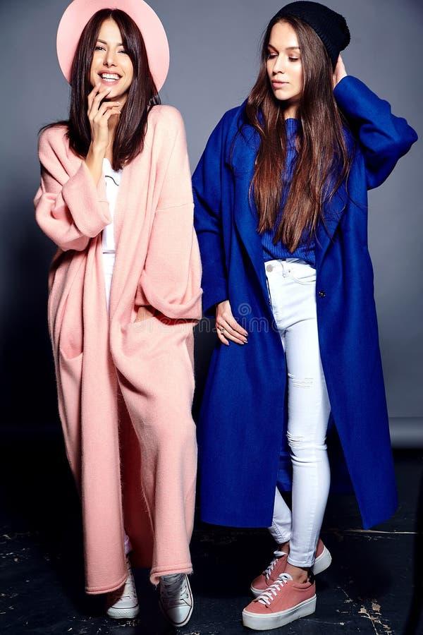 Donkerbruine vrouwenmodellen in de overjas van de zomer het toevallige hipster stellen op grijze achtergrond stock foto