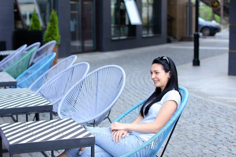 Download Donkerbruine Vrouwenzitting Als Voorzitter Bij Straatkoffie Stock Afbeelding - Afbeelding bestaande uit outdoors, rust: 114227025