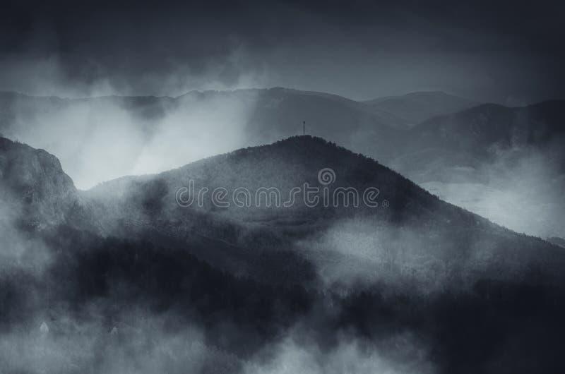 Donkere berg met mist in koude ochtend stock foto