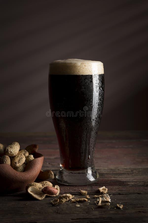 Donkere bier en pinda's stock afbeelding