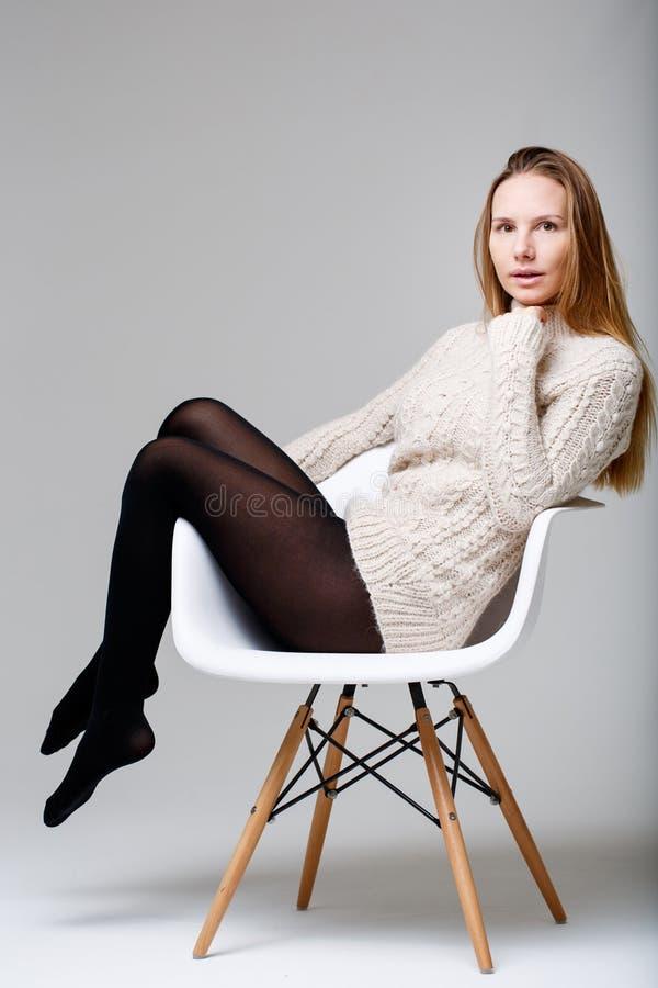 Donkere blondezitting in studio stock afbeeldingen