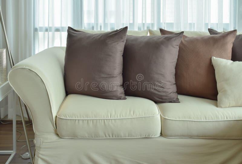 Donkere bruine hoofdkussens die op beige kleurenbank plaatsen royalty-vrije stock foto