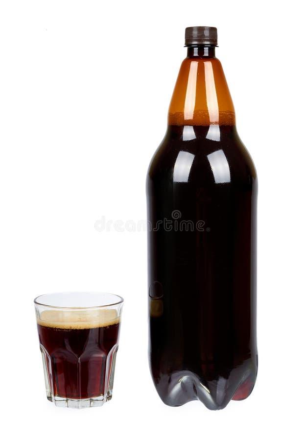 Donkere bruine plastic die fles bier of kwas met glaskop op een witte achtergrond wordt geïsoleerd royalty-vrije stock afbeeldingen