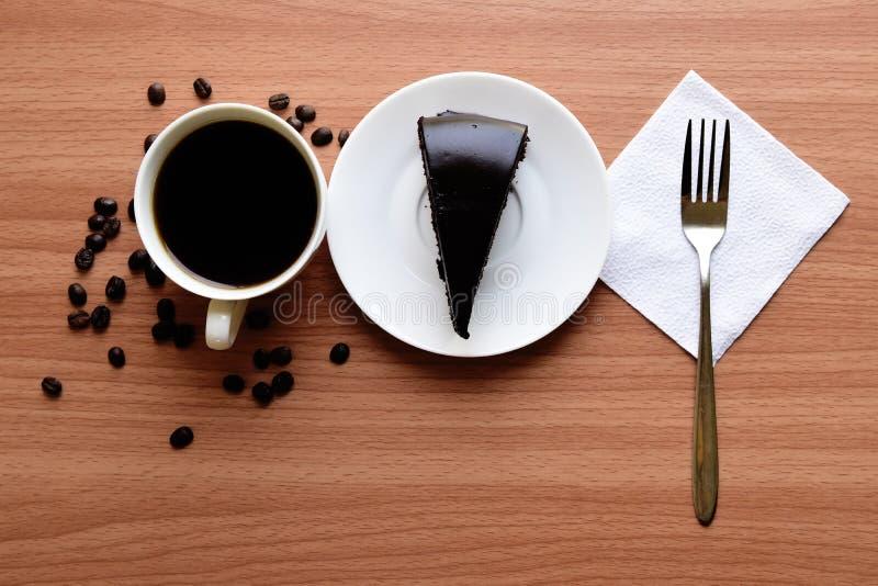 Donkere chocolade en kop van koffieespresso op schotel op houten lijst stock afbeeldingen