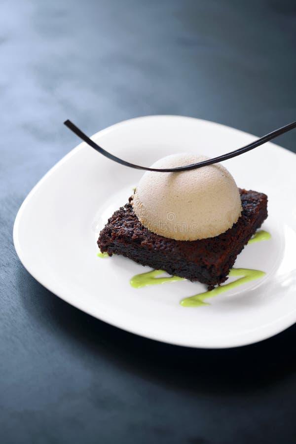 Donkere chocoladebrownie met pralinemousse en pistacheroom stock afbeelding