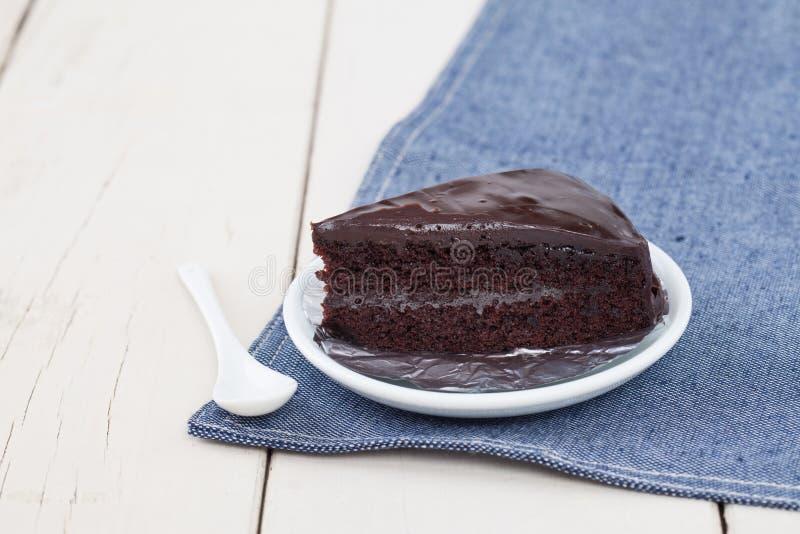 Donkere chocoladecake op witte plaat op houten lijst royalty-vrije stock foto's
