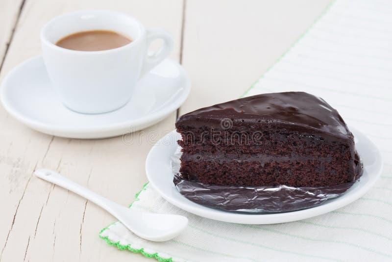 Donkere chocoladecake op witte plaat op houten lijst met koffie stock foto's