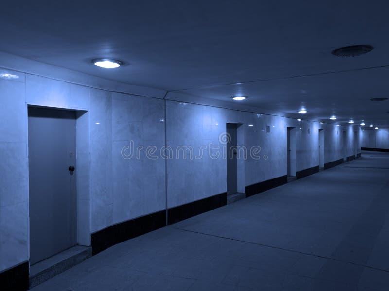 Donkere concrete gang met gesloten deuren stock afbeeldingen