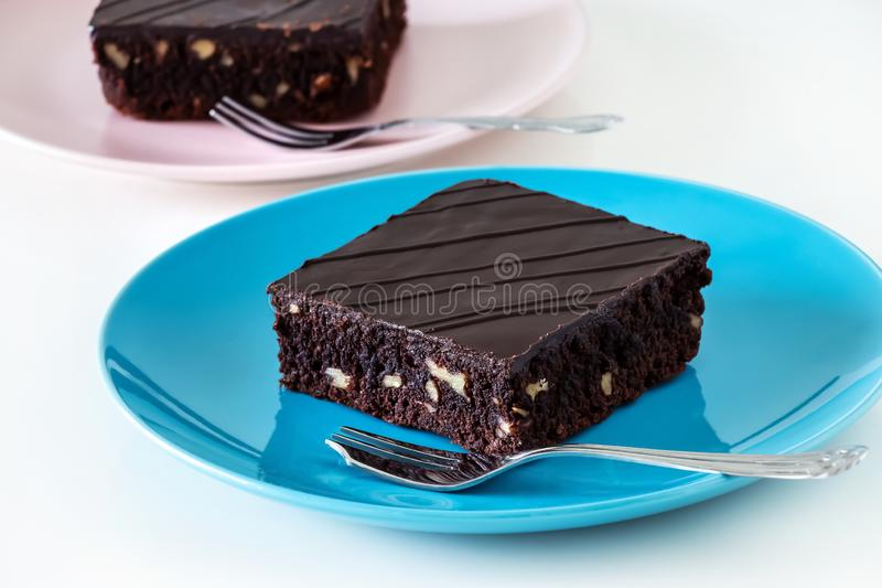 Donkere de browniecake van de chocoladeveganist met witte achtergrond van de noten de blauwe en roze plaat stock afbeeldingen