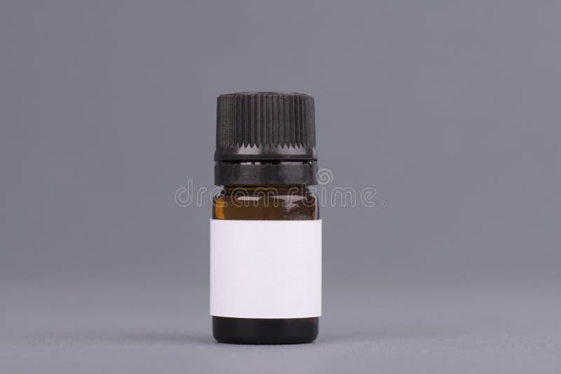 Donkere de flessenkruik van het geneeskundeglas, etherische olie bruine fles Spot op fles met druppelbuisje Container voor parfum stock afbeelding