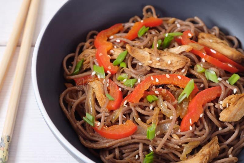 Donkere deegwaren met gestoomde groenten en geroosterde kip Heerlijke boekweitnoedels met groenten en kip stock afbeelding
