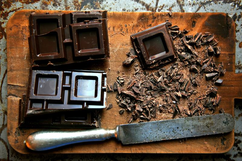 Donkere die chocolade op een houten raad wordt gehakt stock afbeeldingen