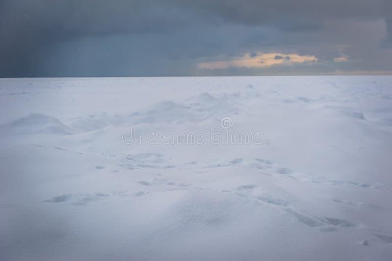 Donkere die wolken en het bevriezen overzees met sneeuw wordt behandeld stock foto