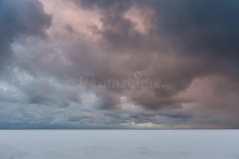 Donkere die wolken en het bevriezen overzees met sneeuw wordt behandeld somethere dichtbij Tallinn, Estland sneeuwstorm royalty-vrije stock foto's