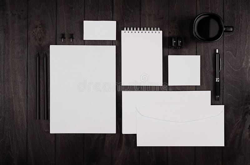 Donkere elegantie het werk ruimte met lege blocnote, briefhoofd, adreskaartje, koffiekop en oortelefoon op zwarte houten plankach stock fotografie