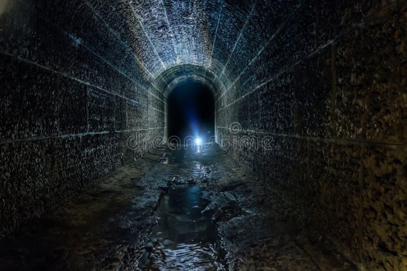 Donkere en griezelige oude historische gewelfde overstroomde ondergrondse drainagetunnel royalty-vrije stock foto's