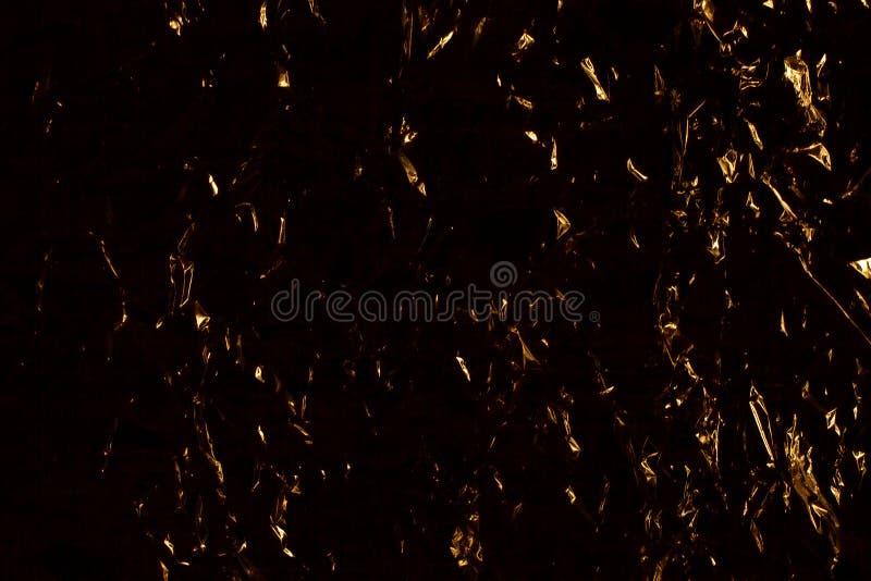 Donkere gele en zwarte abstracte achtergrond, gouden het glanzen metaaloppervlakte, het verfrommelde gouden ontwerp van de metaal stock afbeeldingen